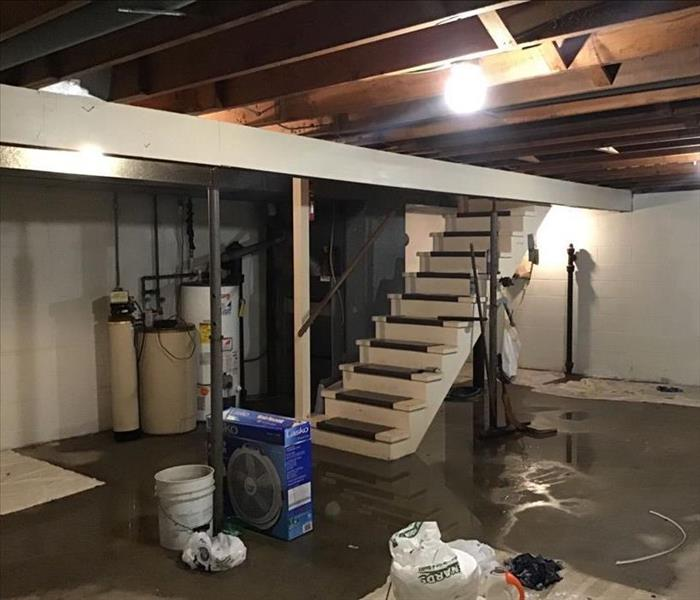 Unfinished basement with water on the floor.