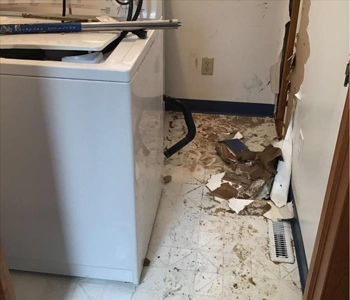 Laundry room in shambles after water damage. Drywall and water are present on the floor