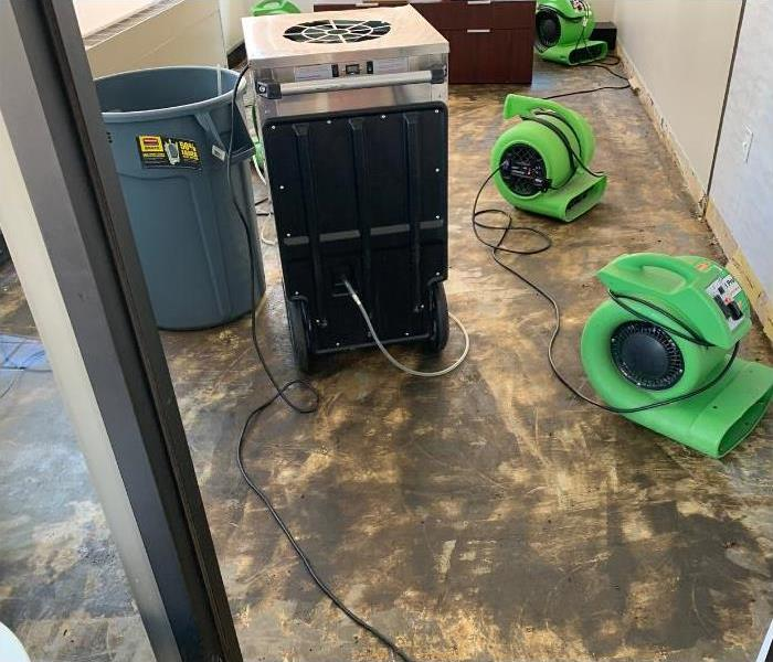 Wet carpet has been removed and air movers are placed for the drying process.