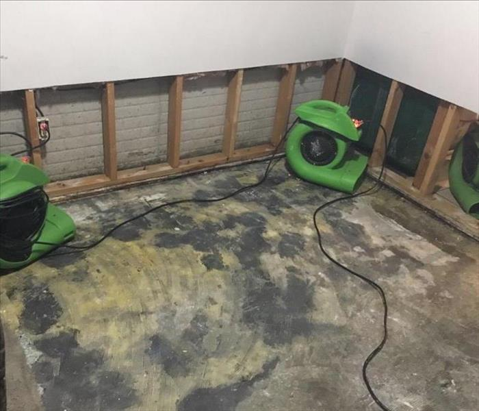 Air movers placed in a room drying inside the walls and removing all moisture from the concrete floor.