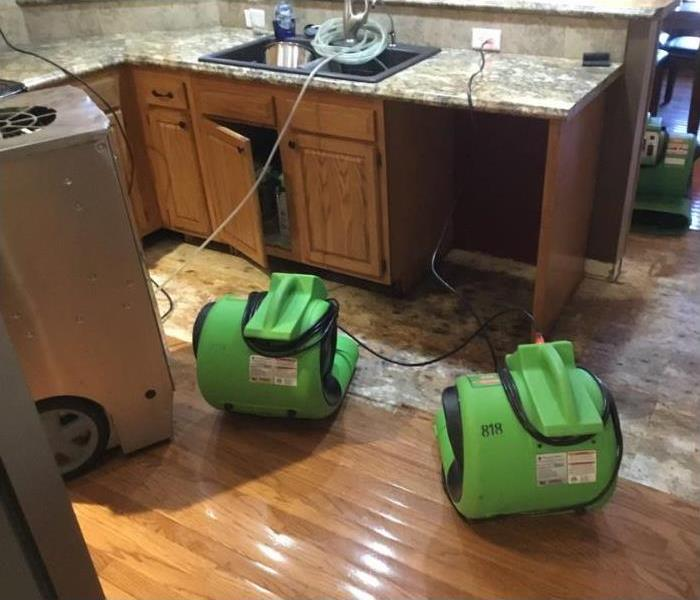 Air movers placed to dry the area damaged by the dishwasher.