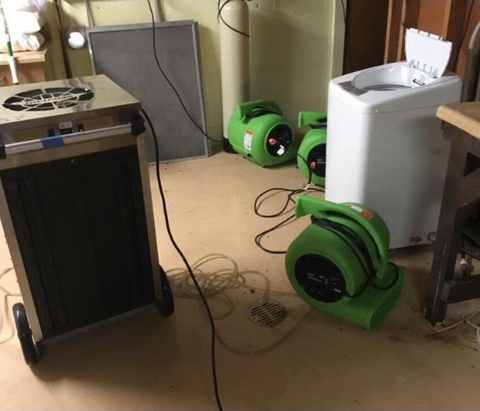 Drying equipment spread throughout the affected area - air movers and dehumidifier.