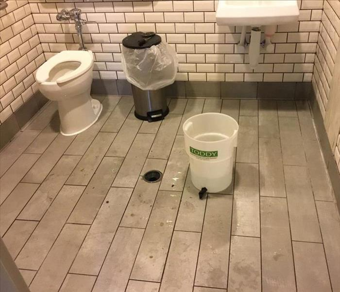 Bathroom floor in business that was affected by water damage.