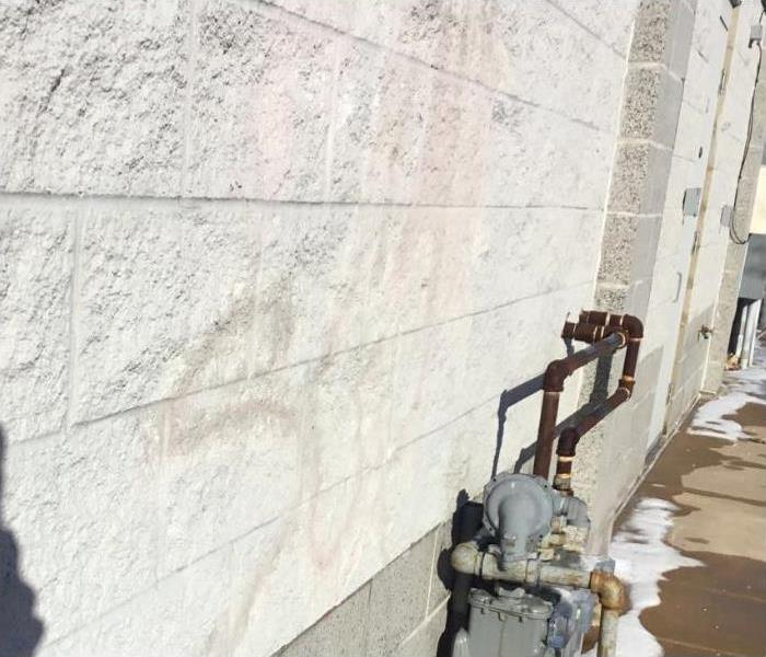 Stains from vandalism on white, outdoor wall of business.