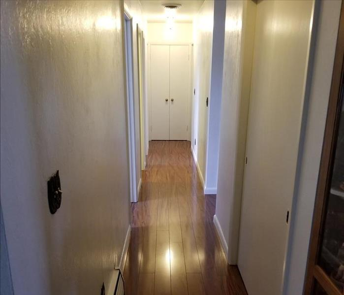 Hallway floor with the flooring and trim replaced.