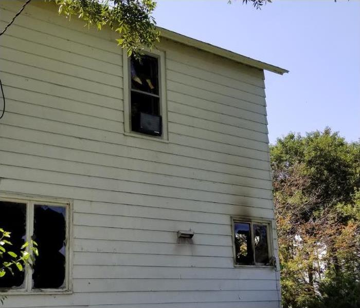 Image of the outside of the house. Smoke stained around the windows from the inside to the outside.