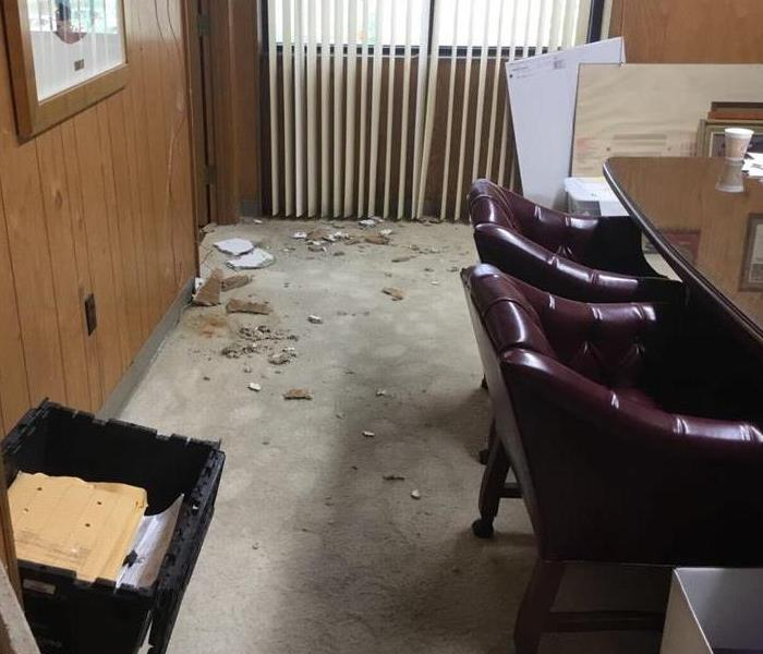 Ceiling experienced water damage and collapsed into an office conference room, leaving water and pieces of tile on the floor.